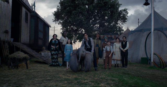 """FAMILY TIES – In Tim Burton's all-new, live-action reimagining of """"Dumbo,"""" Holt Farrier (Colin Farrell), with the help of his children Milly (Nico Parker) and Joe (Finley Hobbins), is called on to take care of a newborn elephant whose oversized ears make him a laughingstock in an already struggling circus. Holt's circus family includes Miss Atlantis (Sharon Rooney), Rongo (DeObia Oparei), Pramesh's nephew (Ragevan Vasan), Pramesh Singh (Roshan Seth), Catherine the Greater (Zenaida Alcalde) and Ivan the Wonderful (Miguel Muñoz). """"Dumbo"""" opens in theaters on March 29, 2019. © 2018 Disney Enterprises, Inc. All Rights Reserved."""